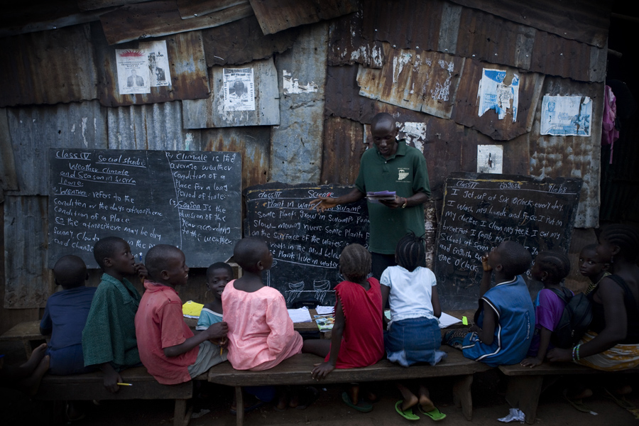 A class is taught in a narrow passage in Kroo Bay slum. Kroo Bay, Freetown, Sierra Leone.